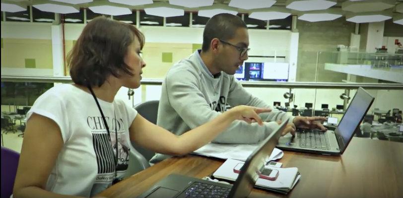 Mercedes Agüero (periodista) y Daryl Zúniga, ingeniero en Sistemas de la Unidad, en pleno trabajo colaborativo.